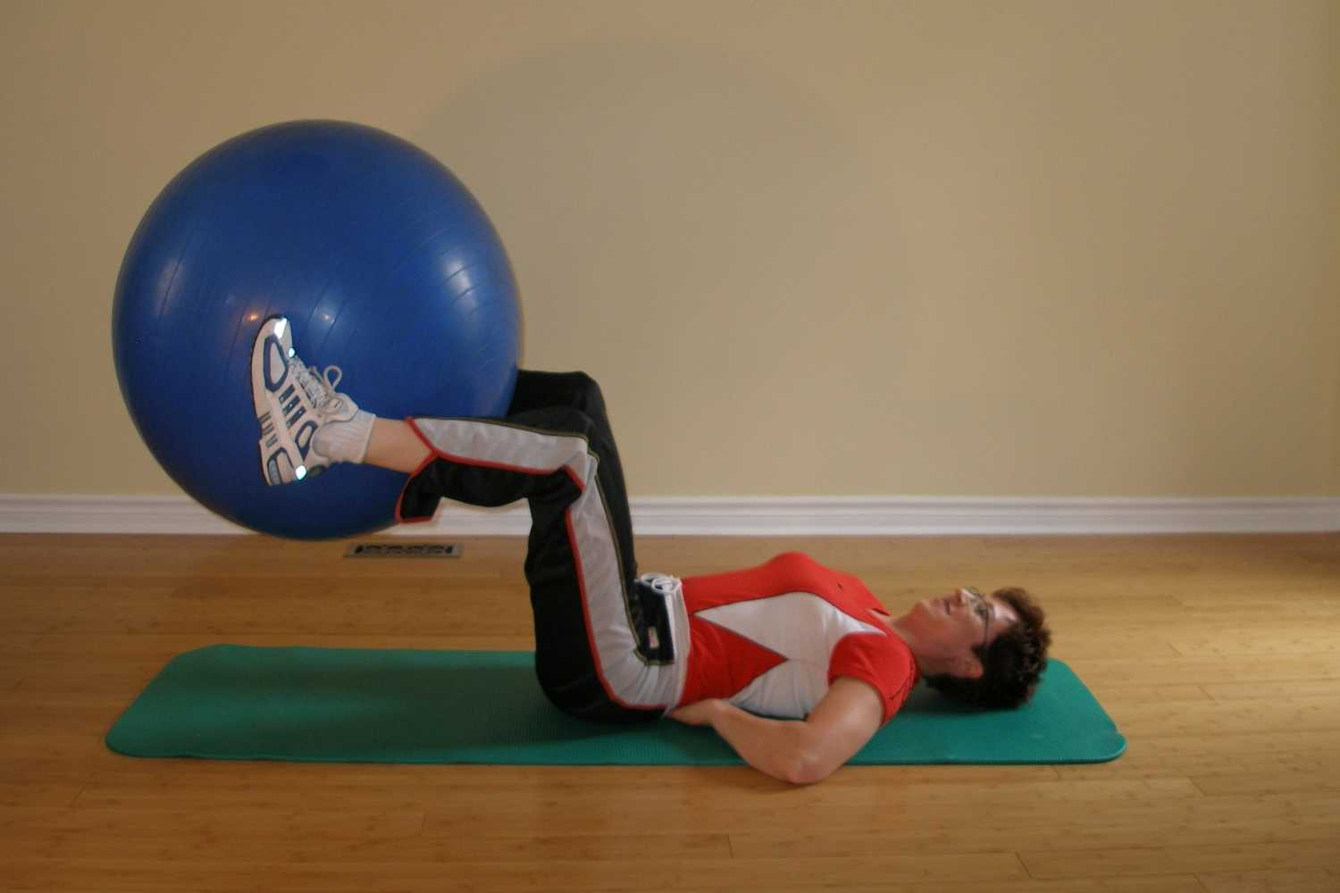 lower the exercise ball while keeping knees stationary