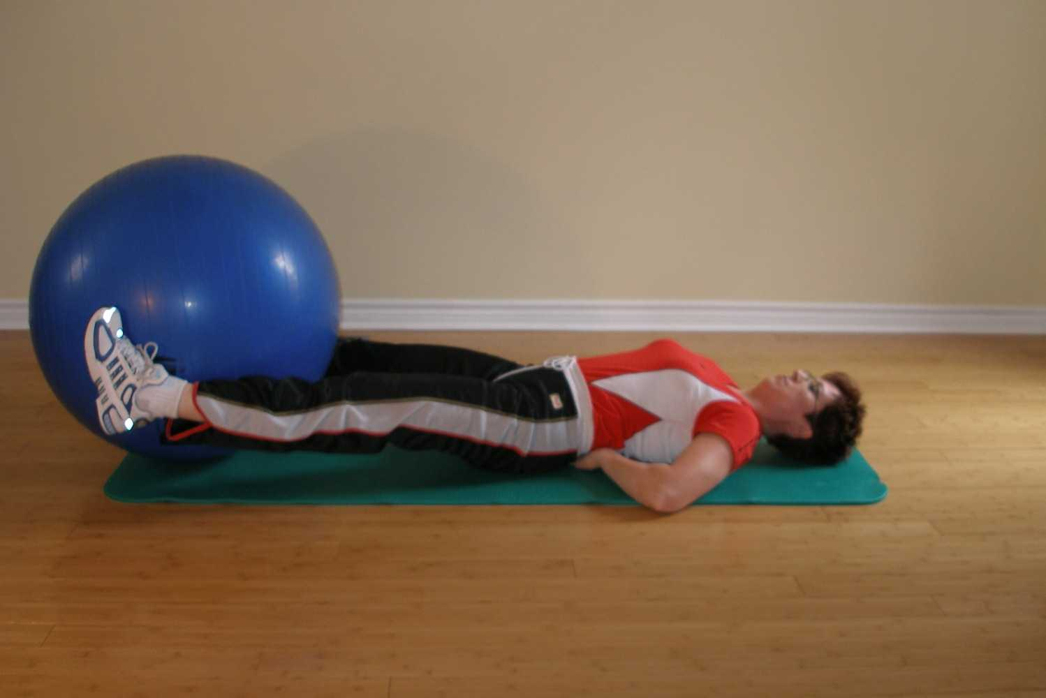 straight leg hip crunch using the exercise ball top position