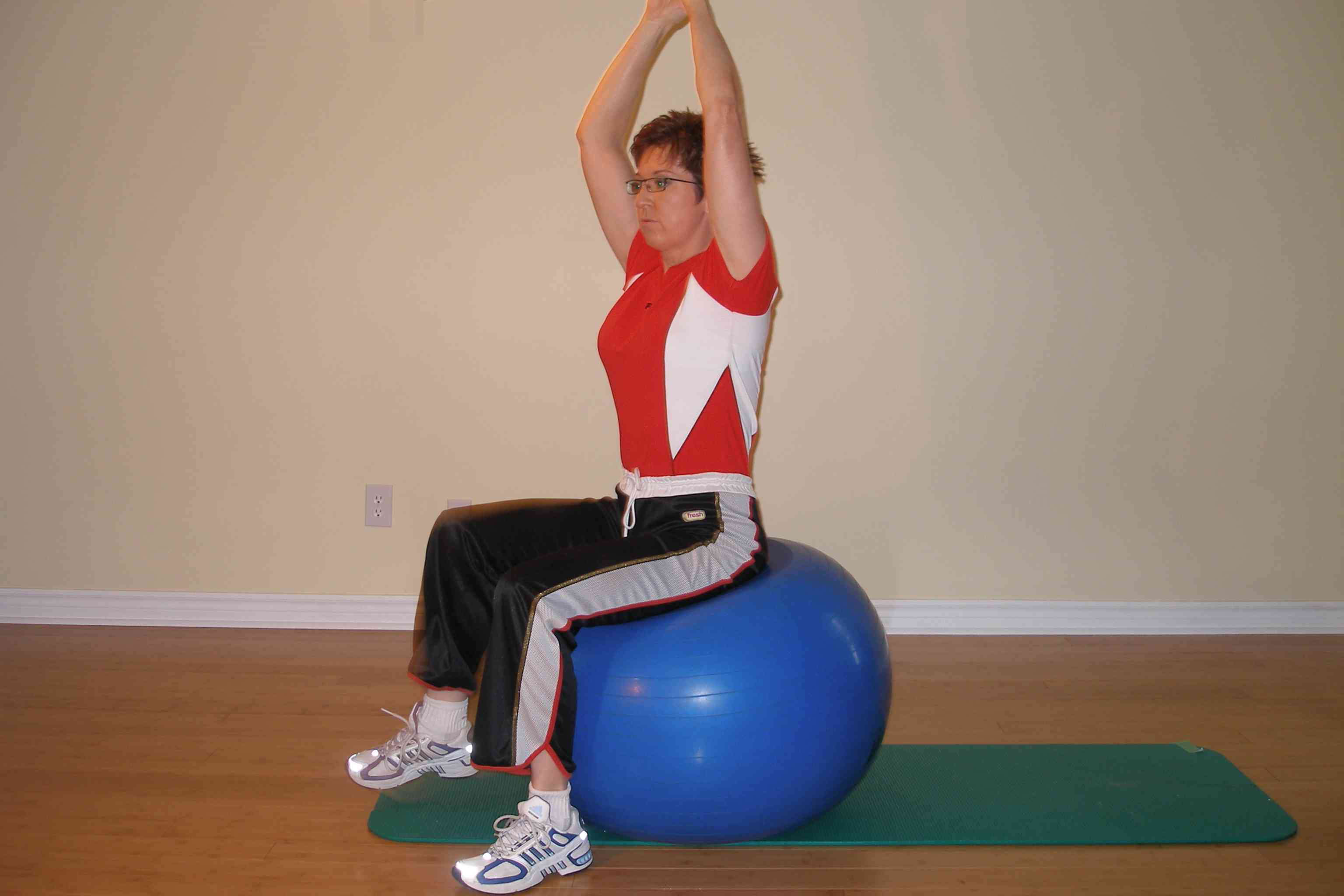 single leg raise on the exercise ball with arms up start