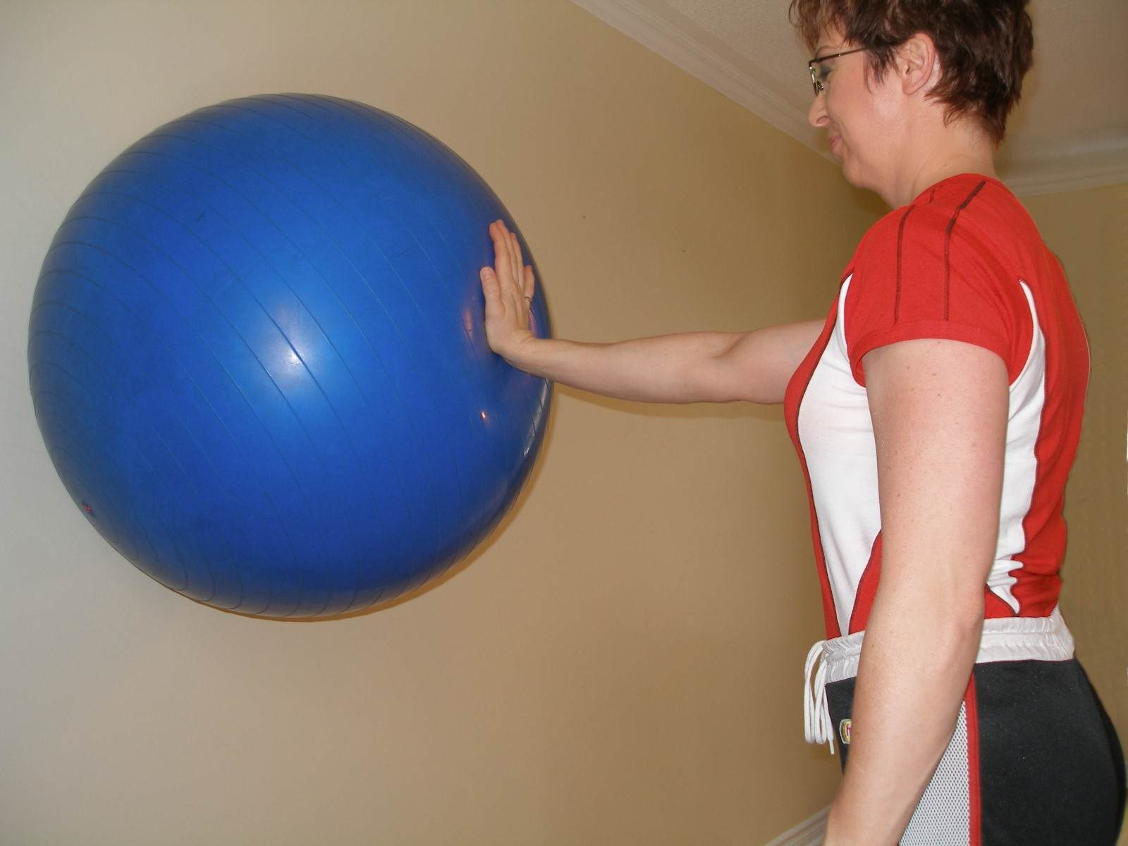 single arm standing plank on the exercise ball
